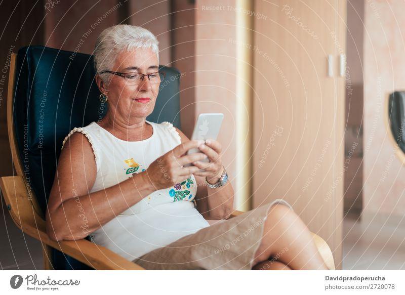 Ältere Frau auf dem Handy zu Hause graue Haare PDA alt heimwärts Mitteilung in den Ruhestand getreten Mensch Technik & Technologie Freizeit & Hobby sitzen