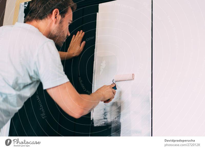 Mann bemalt eine Garderobe malen diy Farbroller Überarbeitung Pinsel Kaukasier Design Glück Rückansicht horizontal heimwärts Holz Transformation Feldfrüchte