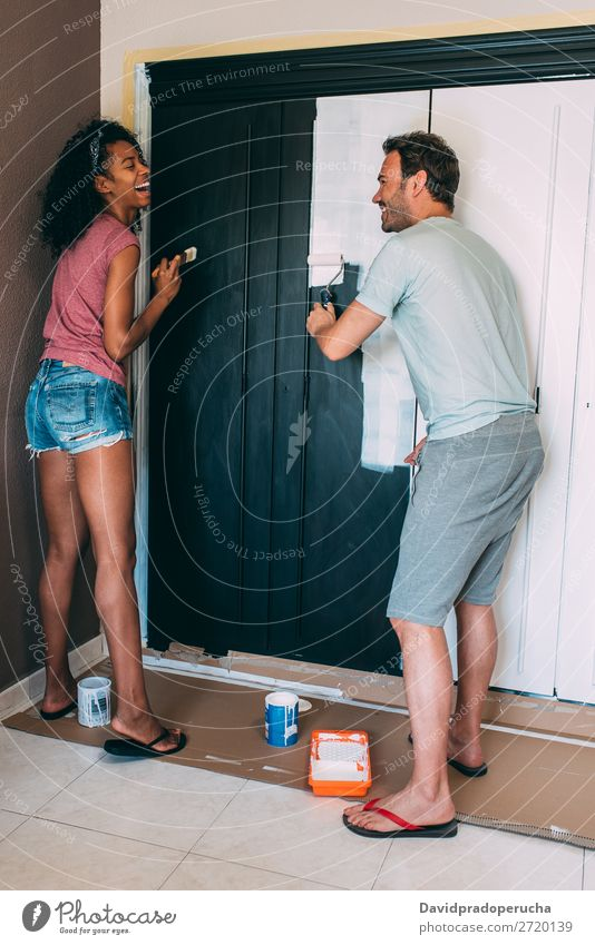 Interrassisches Paar, das einen Kleiderschrank bemalt. malen Partnerschaft Pinsel Design heiter 2 Glück