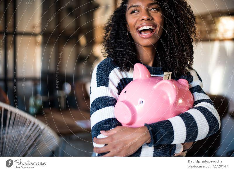 Schwarze Frau umarmt ihr Sparschwein. Spardose Einsparungen Erfolg Business Bargeld schwarz Geld Geldmünzen US-Dollar schön Glück heiter Investition Vermögen
