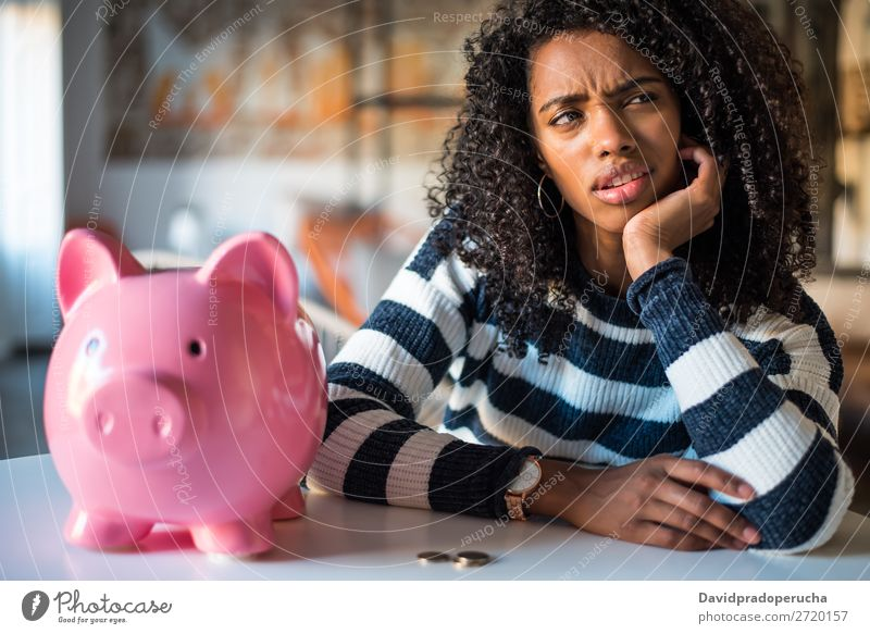 Nachdenklich verwirrte schwarze Frau mit Spardose Fürsorge Schulden Krise Ausdruck Irritation Fehler Traurigkeit Haushaltsplan beunruhigt enttäuscht