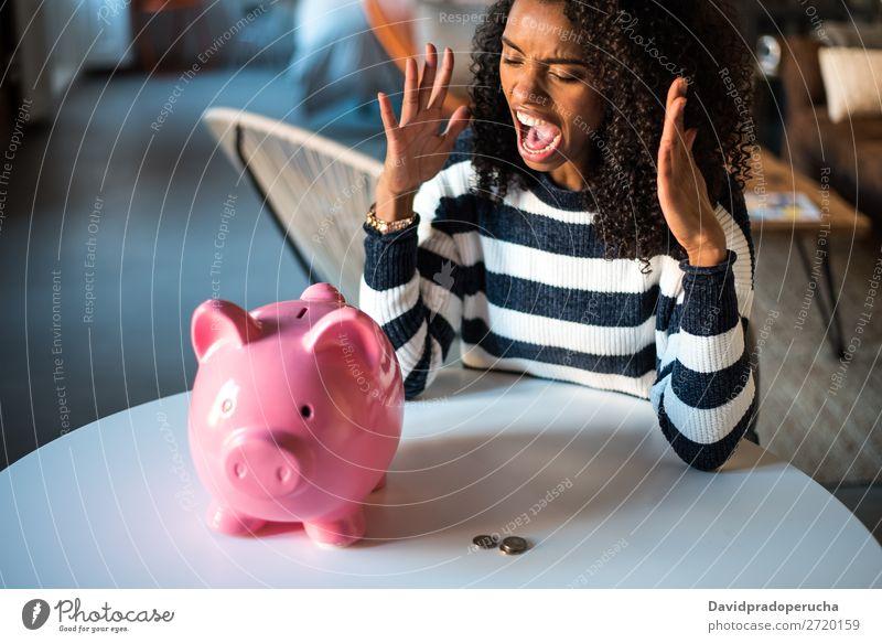 Schwarze unglückliche Frau wütend auf das Sparschwein Spardose Einsparungen Krise Traurigkeit Wut Stress Gefühle verärgert schreien Ärger Ausdruck frustriert
