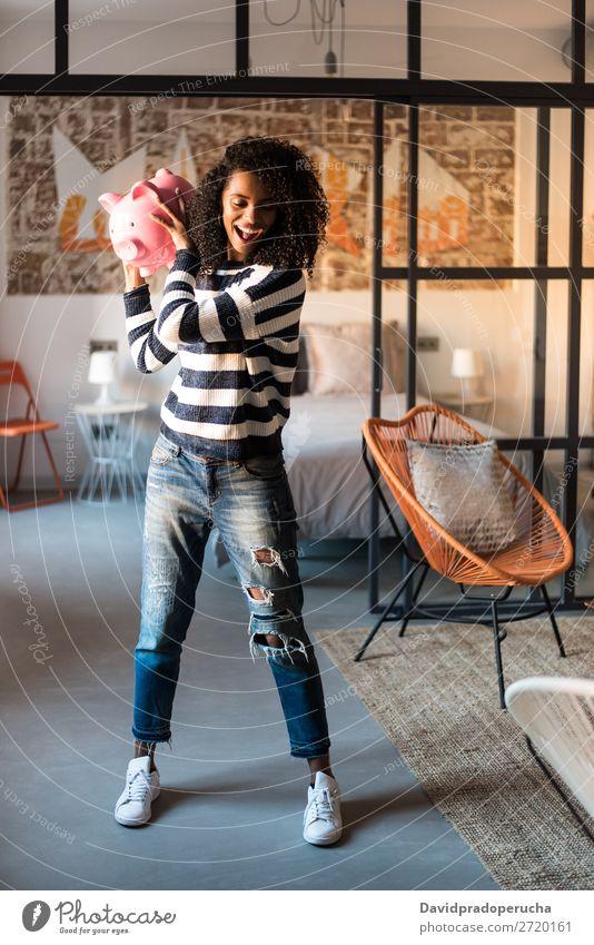 Schwarze Frau zerbricht ihr Sparschwein Spardose Einsparungen Erfolg Business Bargeld schwarz Geld Geldmünzen US-Dollar Pfund Sterling schön Glück Euro heiter
