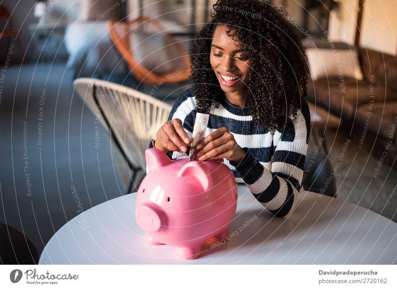 Schwarze Frau mit Sparschweinbank Spardose Einsparungen Erfolg Business Bargeld schwarz Geld Geldmünzen Pfund Sterling schön Glück heiter Investition Vermögen