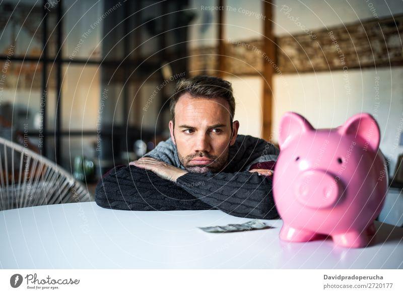 Trauriger frustrierter Mann mit Sparschwein Spardose Schulden Krise Traurigkeit Haushaltsplan Wut beunruhigt Kapitalwirtschaft verärgert Stress Fürsorge