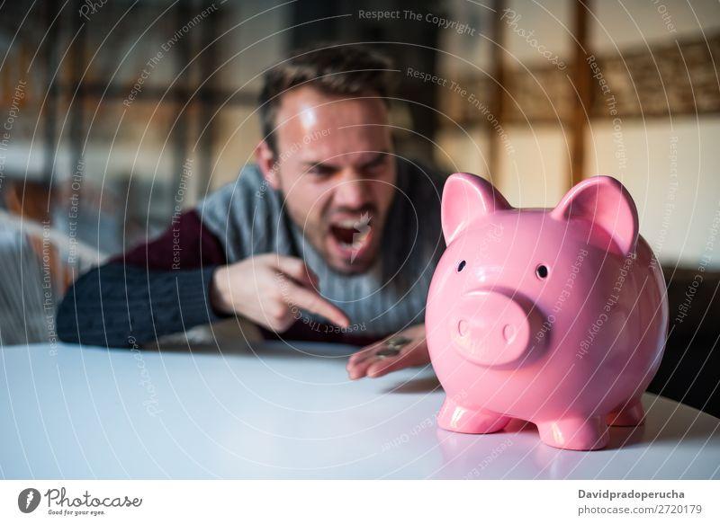 Unglücklicher Mann wütend auf sein Sparschwein Spardose Einsparungen Krise Traurigkeit Wut Stress Gefühle verärgert schreien Ärger Ausdruck frustriert