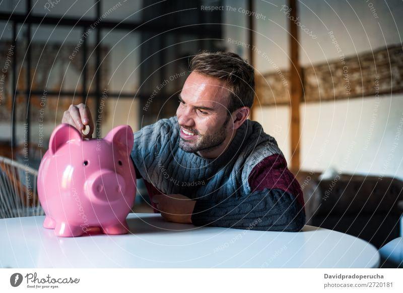 Glücklicher junger Mann mit Sparschweinbank Spardose Einsparungen Erfolg Business Bargeld Kaukasier Geld Geldmünzen Euro schön heiter Investition Vermögen