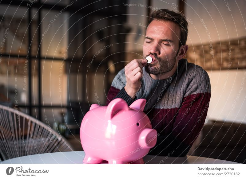 Junger Mann, der eine Münze mit einem Sparschwein küsst. Spardose Einsparungen Erfolg Business Bargeld Kaukasier Geld Geldmünzen Euro schön Glück heiter