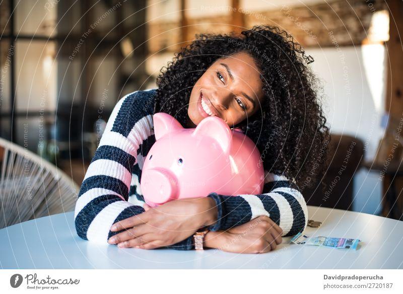 Schwarze Frau umarmt ihr Sparschwein. Spardose Einsparungen Erfolg Business Bargeld schwarz Geld Geldmünzen Euro schön Glück heiter Investition Vermögen