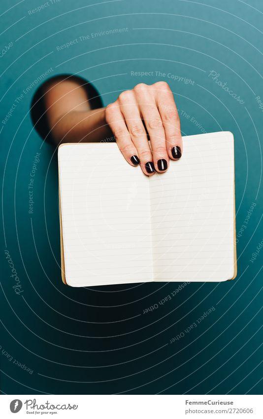 Hand of a woman holding a notebook in the camera feminin 1 Mensch Schreibwaren Papier Kreativität Notizbuch liniert türkis Nagellack leer schreiben Design Kreis