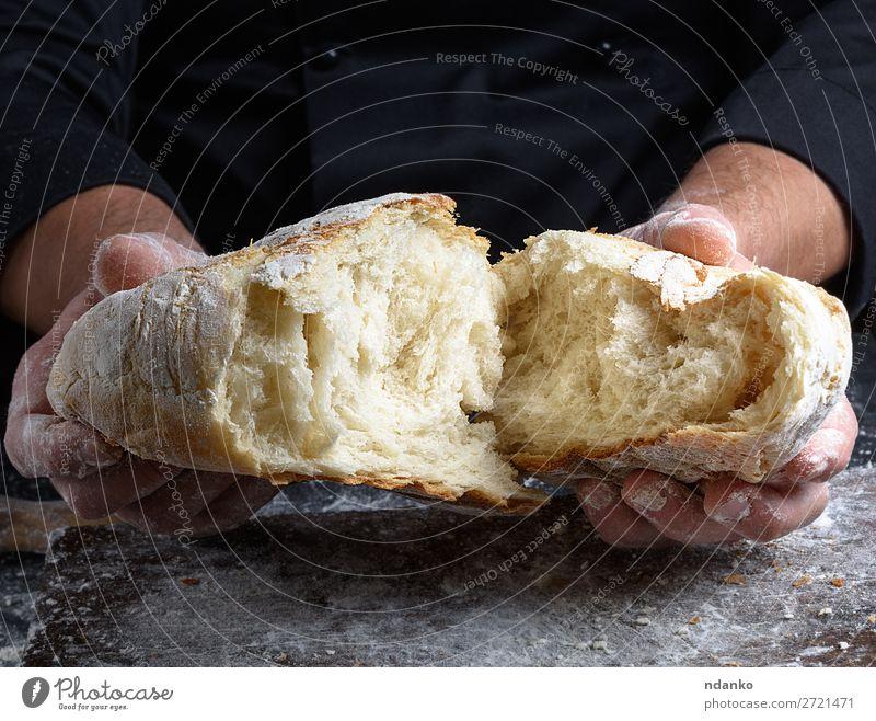frisch gebackenes Weißweizenmehlbrot Teigwaren Backwaren Brot Ernährung Tisch Küche Mensch Hand Finger Holz machen dunkel braun schwarz weiß Tradition Bäcker