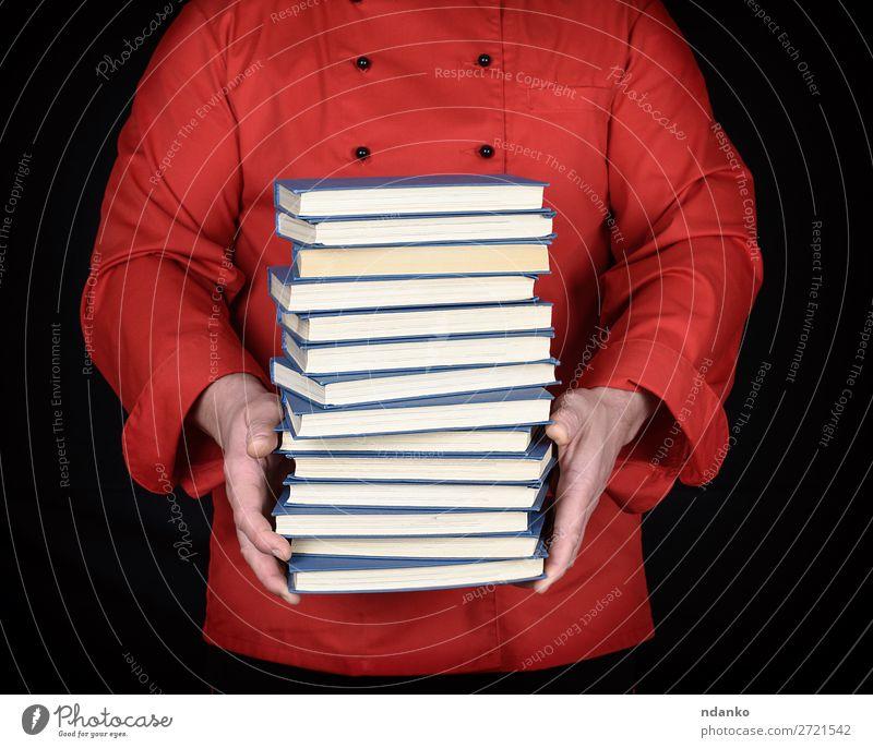 Mann in roter Uniform hält einen Stapel Bücher. elegant Küche Schule lernen Beruf Koch Erwachsene Hand Buch Bibliothek Bekleidung Jacke Papier stehen schwarz