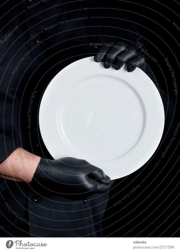 Koch in schwarzer Uniform mit einem runden leeren Teller. Küche Restaurant Beruf Mensch Mann Erwachsene Hand Handschuhe dunkel weiß Kaukasier Küchenchef