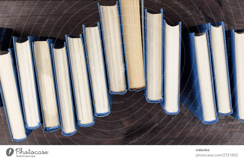 Stapel von Büchern in einem blauen Umschlag lesen Tisch Wissenschaften Schule Studium Menschengruppe Buch Bibliothek Papier Sammlung Holz braun gelb Weisheit