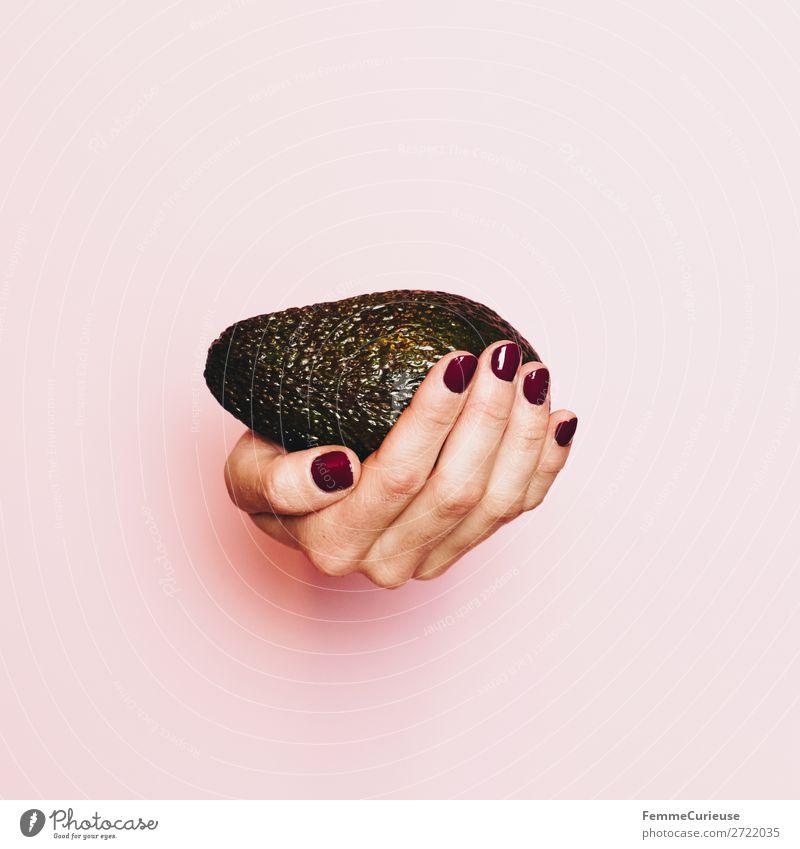 Hand of a woman with avocado in front of pink background Lebensmittel Ernährung Frühstück Mittagessen Abendessen Büffet Brunch Picknick Bioprodukte