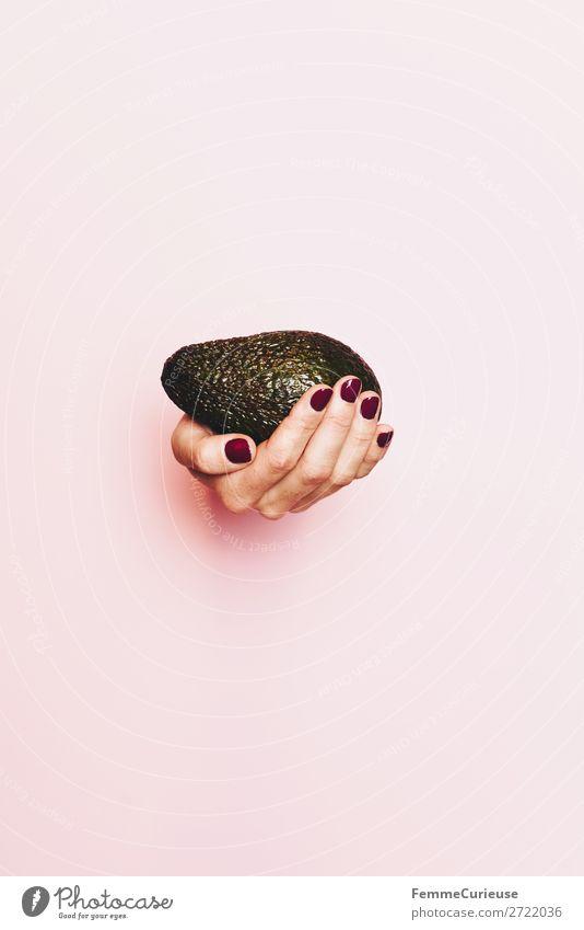 Hand of a woman holding an avocado Lebensmittel Ernährung genießen Gesunde Ernährung Vegetarische Ernährung Vegane Ernährung Avocado festhalten rosa Nagellack