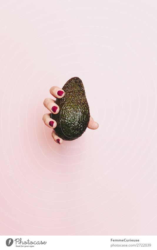 Hand of a woman holding an avocado Lebensmittel Ernährung Frühstück Abendessen Picknick Bioprodukte Vegetarische Ernährung Diät Gesundheit Gesunde Ernährung