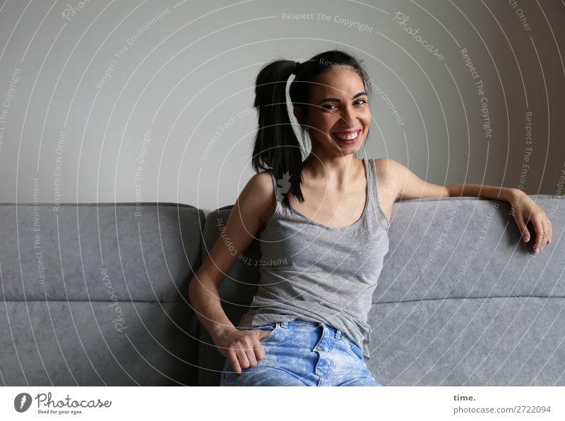 GizzyLovett Sofa Raum feminin Frau Erwachsene 1 Mensch T-Shirt Jeanshose schwarzhaarig langhaarig Zopf festhalten Lächeln lachen Blick sitzen Freundlichkeit