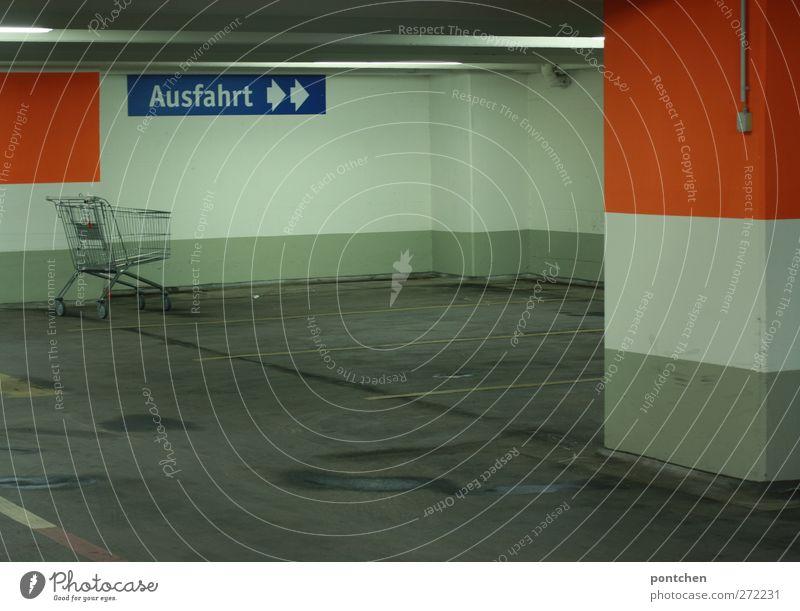 Tiefgarage von innen. Ausfahrt Schild. Parkmarkierungrn, leerer Einkaufswagen. Neonröhren,. Dreckig und hässlich dunkel Schilder & Markierungen Pfeil orange