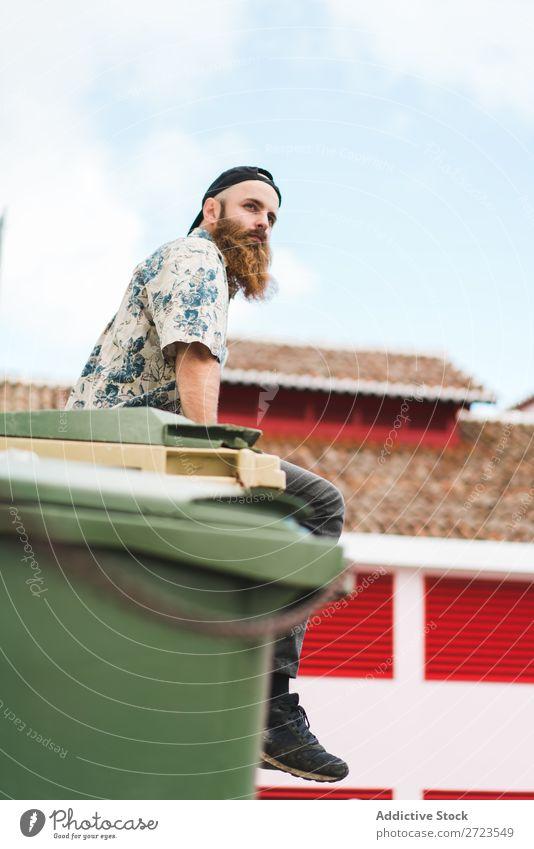 Bartiger Mann auf Müllcontainer sitzend Großstadt Straße Müllbehälter Container Lifestyle