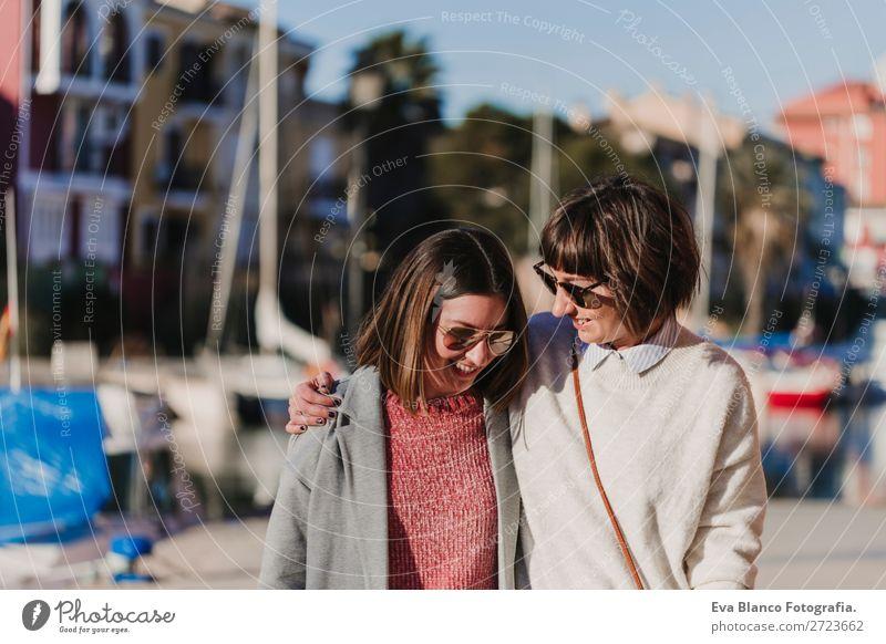 Zwei glückliche Freunde, die an der Straße vorbeigehen. Lifestyle Freude Glück Leben Sonne Sitzung sprechen Frau Erwachsene Familie & Verwandtschaft