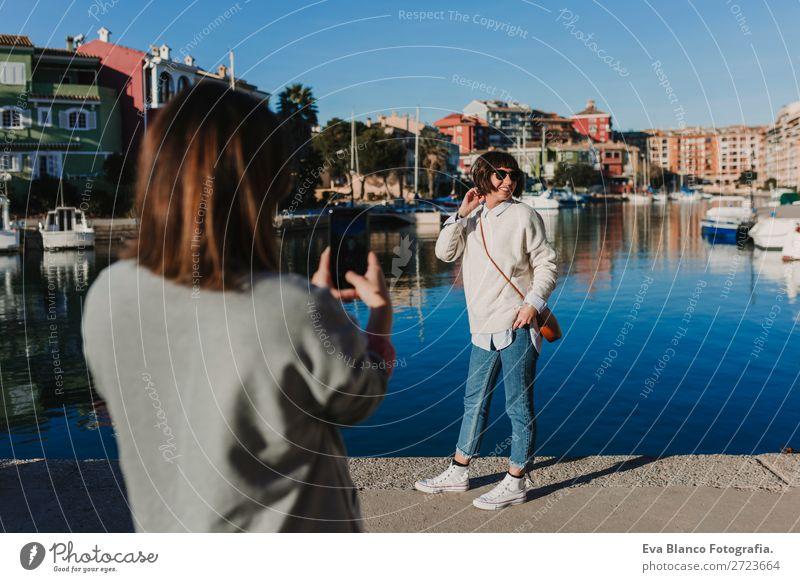 zwei Freunde auf der Straße, die mit dem Handy Fotos machen. Lifestyle Freude Glück schön Schminke Sonne Technik & Technologie Frau Erwachsene Freundschaft