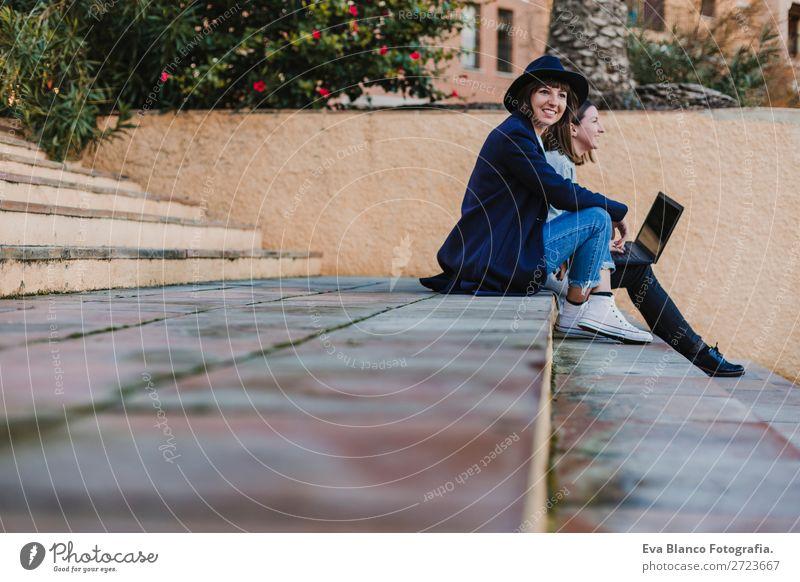 zwei Freundinnen, die im Freien auf der Treppe sitzen und den Laptop benutzen. Glück schön Erholung Ferien & Urlaub & Reisen Sonne Studium