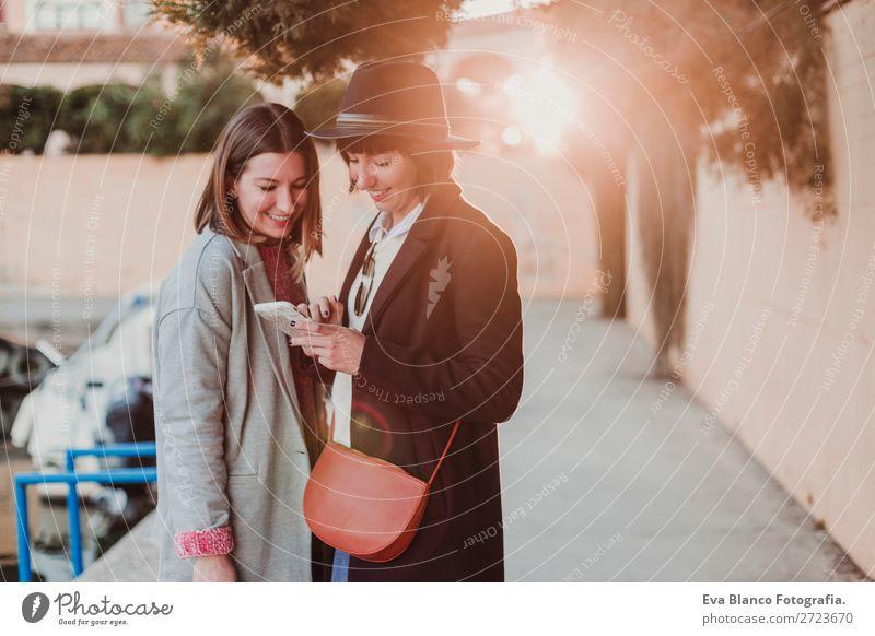 zwei schöne Frauen mit Sonnenuntergang Glück Erholung Ferien & Urlaub & Reisen Studium Arbeit & Erwerbstätigkeit Handy Computer Notebook Technik & Technologie