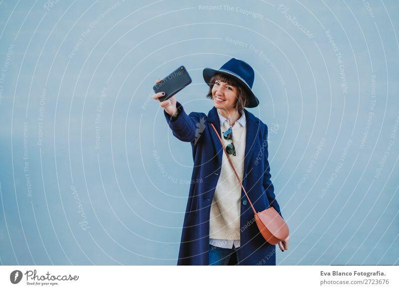 Porträt einer jungen, schönen Frau im Freien Lifestyle Stil Glück Handy Technik & Technologie Internet Erwachsene Herbst Stadt Straße Mode Bekleidung