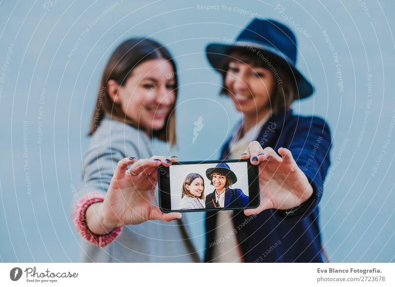 zwei Freunde im Freien mit stylischer Kleidung, die ein Selfie mitnehmen. Lifestyle Stil Glück schön Handy Technik & Technologie Internet Frau Erwachsene