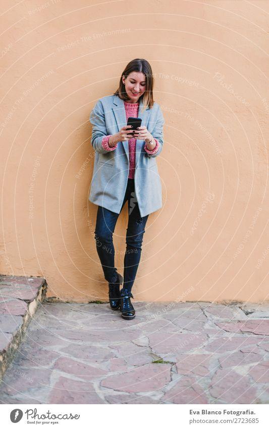 Porträt einer jungen schönen Frau im Freien Lifestyle Stil Glück Handy Technik & Technologie Internet Erwachsene Herbst Stadt Straße Mode Bekleidung