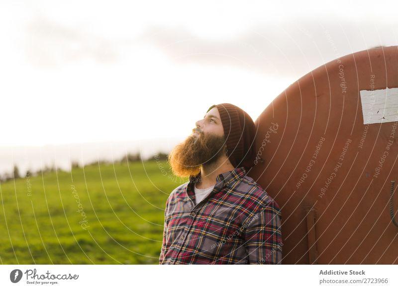 Nachdenklicher Mann, der sich auf das Fass stützt. Tourist Feld grün Landschaft Natur Himmel Sommer bärtig anlehnen Rost alt Wegsehen Fürsorge