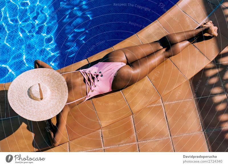 Schwarze Frau, die in einem Swimmingpool liegt. Afrikanisch anonym Rückansicht Barfuß schön schwarz blau Textfreiraum Feldfrüchte urwüchsig gesichtslos Mädchen