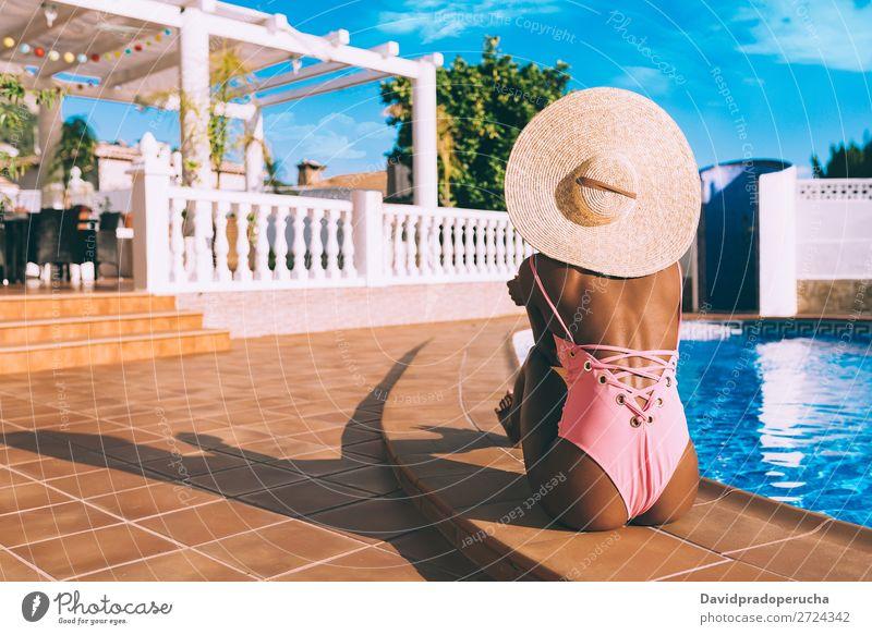 Schwarze Frau sitzt in einem Swimmingpool. schwarz urwüchsig Schwimmbad Sommer Sonnenbad Ferien & Urlaub & Reisen Bräune horizontal Bräunen Erholung
