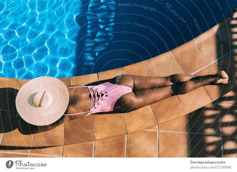 Schwarze Frau, die in einem Swimmingpool liegt. schwarz urwüchsig Schwimmbad Sommer Sonnenbad Ferien & Urlaub & Reisen Bräune horizontal Bräunen Erholung