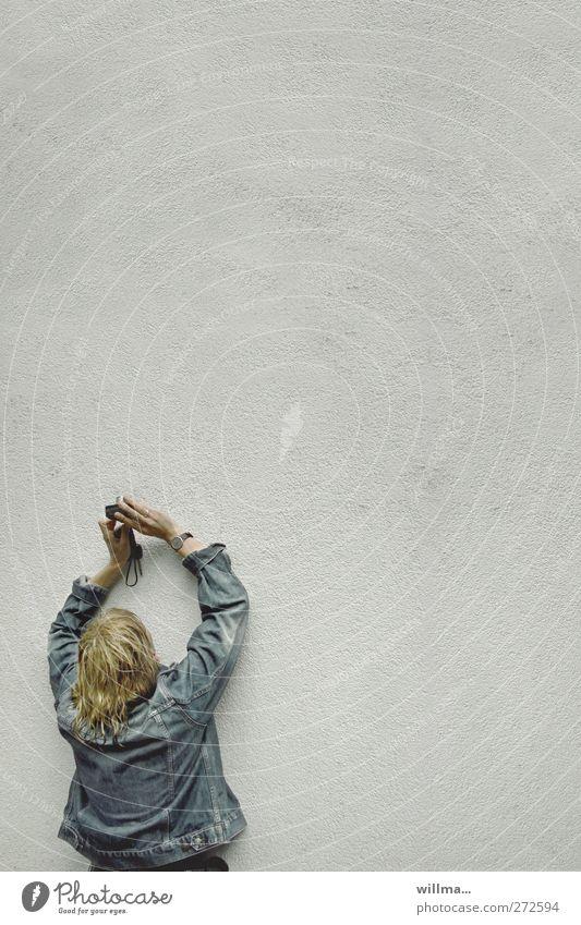 Blonde Frau in Jeansjacke fotografiert eine Wand Fotografieren Freizeit & Hobby Fotokamera Junge Frau Jugendliche Erwachsene Mensch Regen Fassade Jacke blond