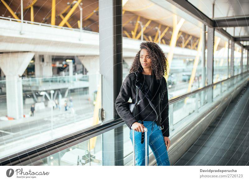 schwarze Frau auf dem Fahrsteig am Flughafen mit einem rosa Koffer. schön Afrikanisch Amerikaner Bewegung Gang Rolltreppe Ausflug Station Gepäck laufen Richtung