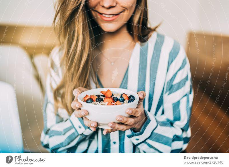Getreidefrau aus der Nähe beim Essen von Hafer und Früchten Schüssel zum Frühstück Schalen & Schüsseln Frau Müsli Haferbrei Hand Feldfrüchte anonym unkenntlich