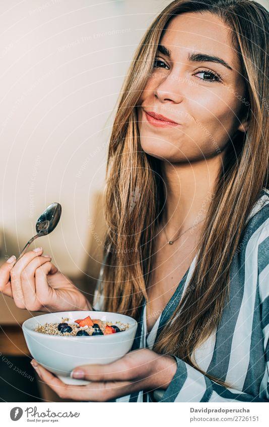 Frau aus der Nähe beim Essen von Hafer und Früchten Schüssel zum Frühstück Schalen & Schüsseln Müsli Haferbrei Hand Lächeln Feldfrüchte Erdbeeren Blaubeeren