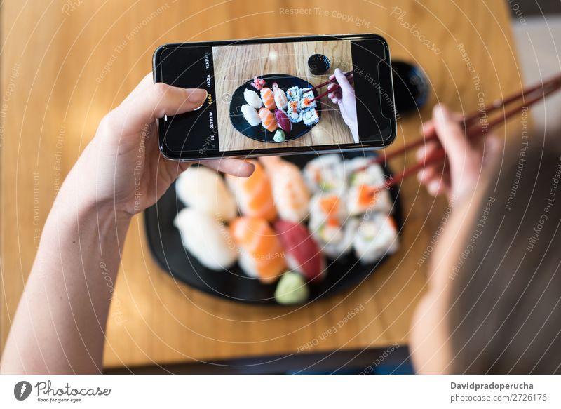 Draufsicht der Frau, die Sushi auf dem Tisch fotografiert. Fotografie PDA Mobile Telefon Schuss Hand