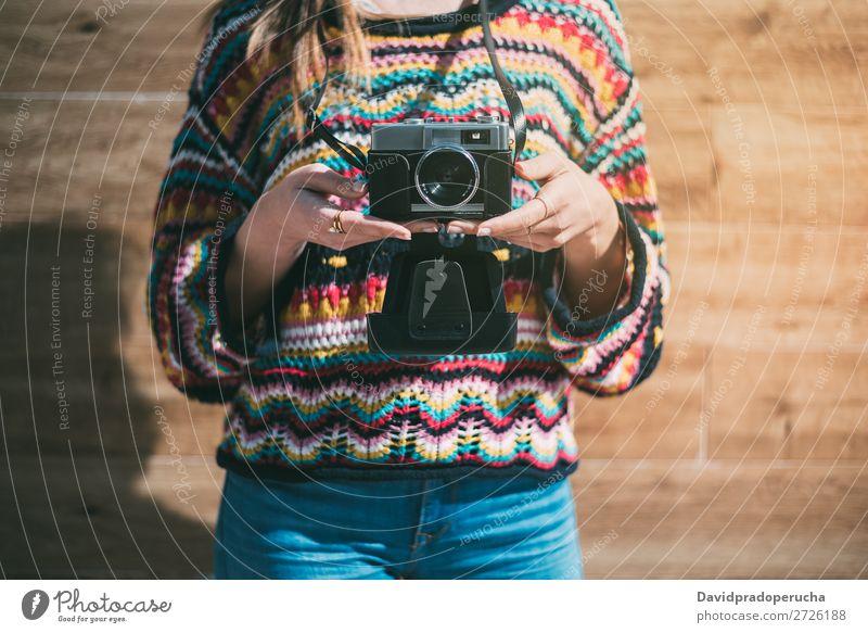 beschnittene Frau mit alter Kamera und buntem Pullover altehrwürdig Fotokamera retro Jugendliche Anschnitt anonym