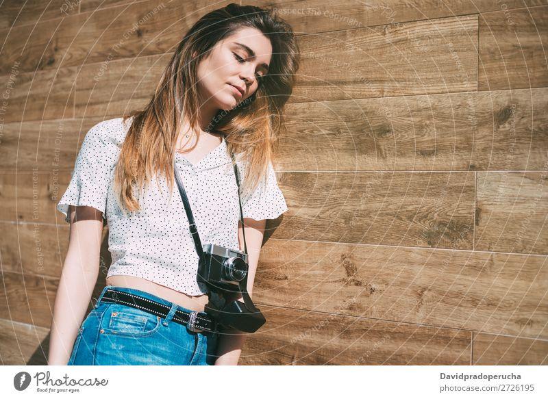 Schöne Frau mit alter Kamera, die an einer Holzwand steht. altehrwürdig Fotokamera retro Jugendliche schön Porträt