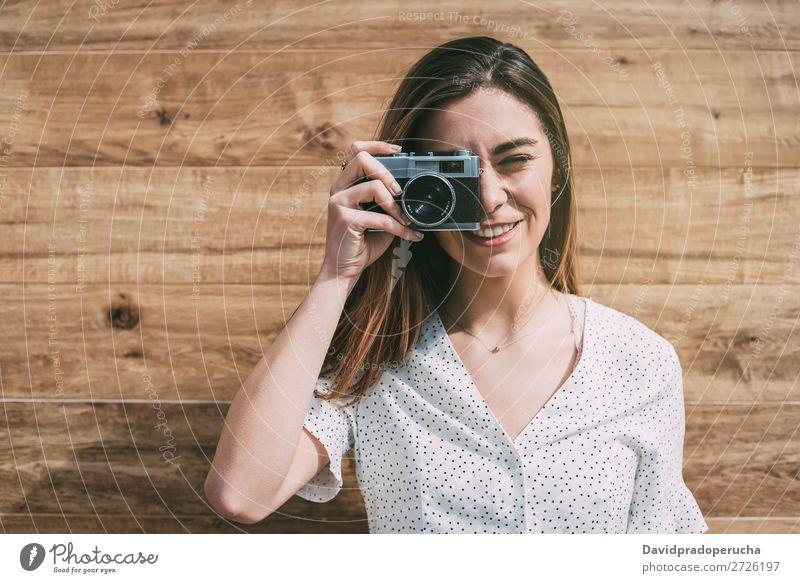 Schöne Frau mit alter Kamera, die Fotos macht. altehrwürdig Fotokamera retro Jugendliche nehmen Schuss auf die Kamera schauen schön Rolle Porträt Fotografie