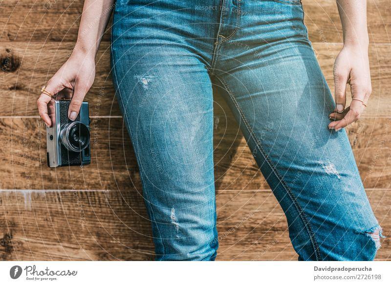 Beschnittene Frau Jeansbeine mit alter alter Kamera altehrwürdig Fotokamera retro Beine Jugendliche Anschnitt