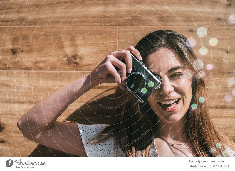 Schöne Frau mit alter Kamera mit Seifenblasen beim Fotografieren. altehrwürdig Fotokamera retro Luftblase Jugendliche nehmen