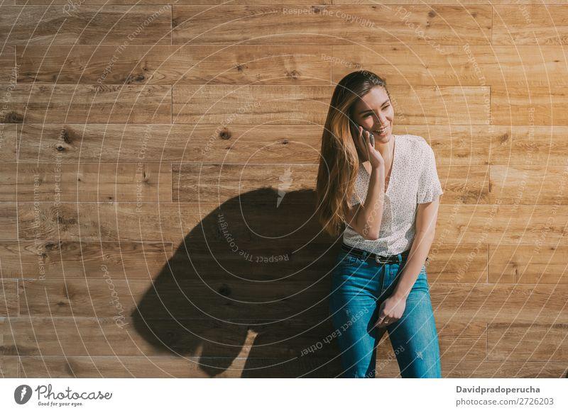 Glückliche Frau mit Smartphone an einer Holzwand PDA Telefon Mobile Mitteilung Gerät Lächeln Wegsehen Porträt Hintergrundbild Sommer Wand Halt klug Jugendliche