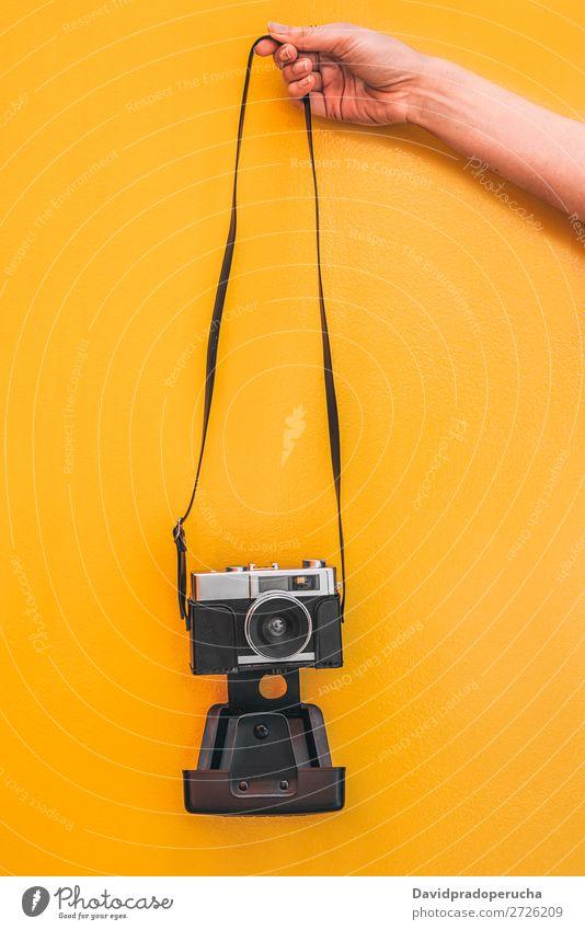 Hand hält eine Vintage-Kamera an der orangefarbenen Wand isoliert. Arme Fotokamera altehrwürdig Orange retro vereinzelt Studioaufnahme Halt Freizeit & Hobby
