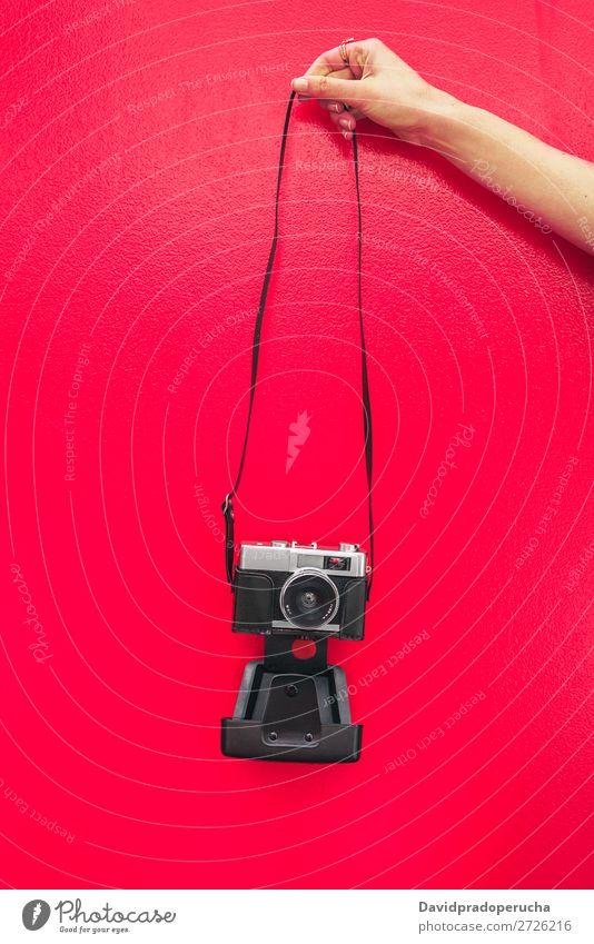 Hand haltend eine Vintage-Kamera isoliert an der roten Wand Arme Fotokamera altehrwürdig rosa retro vereinzelt Studioaufnahme Halt Freizeit & Hobby