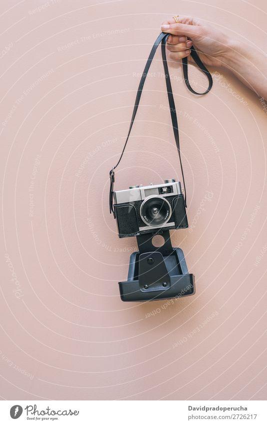 Hand haltend eine Vintage-Kamera isoliert an der rosa Wand Arme Fotokamera altehrwürdig retro vereinzelt Studioaufnahme Halt Freizeit & Hobby