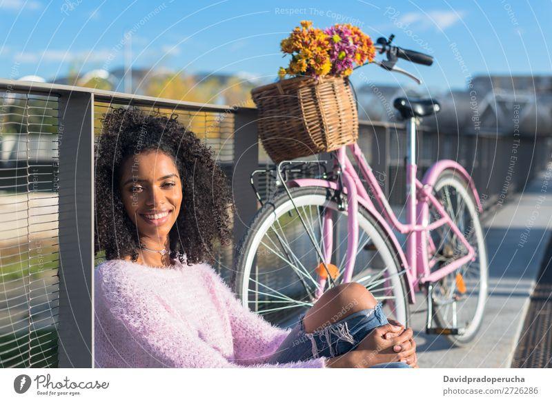 Schwarze junge Frau sitzt mit ihrem alten Fahrrad am Fluss. Mädchen schön retro Blume Glück altehrwürdig Blumenstrauß rosa Sommer Jugendliche hübsch Frühling